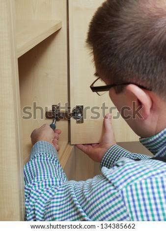 Carpenter fitting wardrobe hinge doors in walk-in closet - stock photo