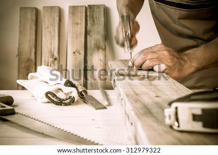 carpenter hammer a nail, vintage style. - stock photo
