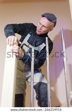 Carpenter Hand Polishing Modern Ladder with Sandpaper - stock photo