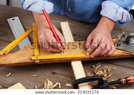 carpenter hand with yardstick and pencil - stock photo