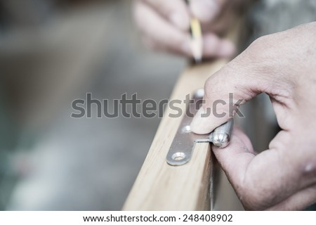 Carpenter hand working over door edge and hinge, shallow depth of field - stock photo