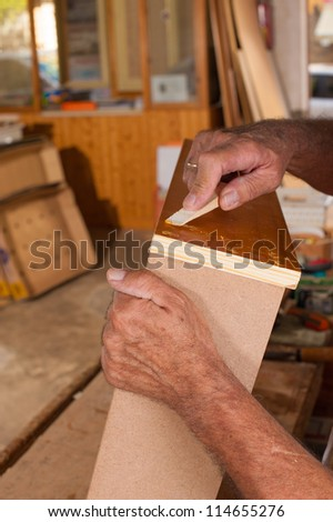 Carpenter hands working at a piece of furniture - stock photo