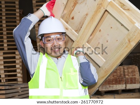 Carpenter lifting pallet in the warehouse - stock photo