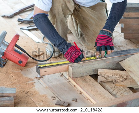 Carpenter man measuring plank of wood for Home Building - stock photo