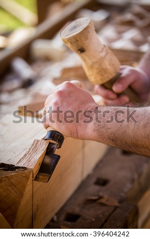 Carpenter master holding a sharp, flat chisel, trimming specific, traditional, hungarian shapes and patterns in wood. - stock photo