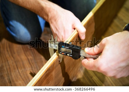 Carpenter measures the thickness of the laminate board with electric calipers during the flooring. - stock photo