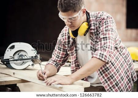 Carpenter measuring a wooden plank - stock photo