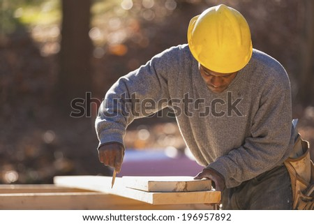 Carpenter measuring and marking bevel cuts on roof rafters for cutting with power tool  - stock photo