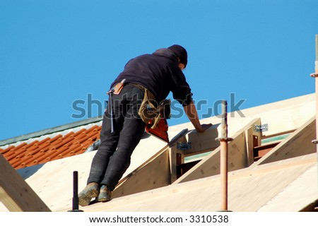carpenter on a roof - stock photo