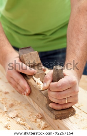 Carpenter or joiner working with traditional plane - closeup