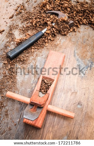 carpenter plane and hammer on the old wood , carpentry background  - stock photo