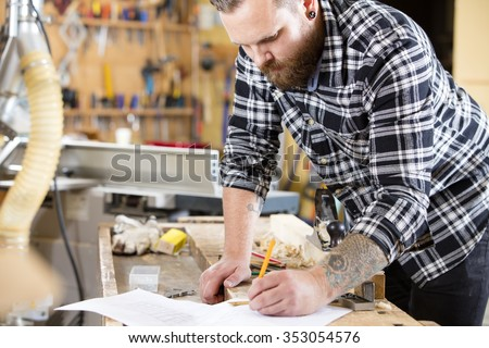 Carpenter plans work and take notes at project drawing - stock photo