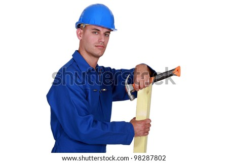 Carpenter posing with plank of wood and hammer - stock photo