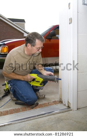 Carpenter repairing exterior door casing, weather & insects have contributed to rot at the bottom of casing - stock photo