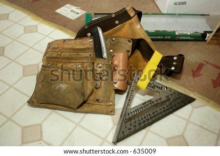 Carpenter's Tool Belt sitting on vinyl flooring - stock photo