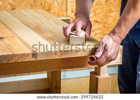 Carpenter sanding  a table - stock photo