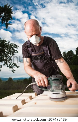 Carpenter sanding a wood with sander with dramatic dark sky background - stock photo