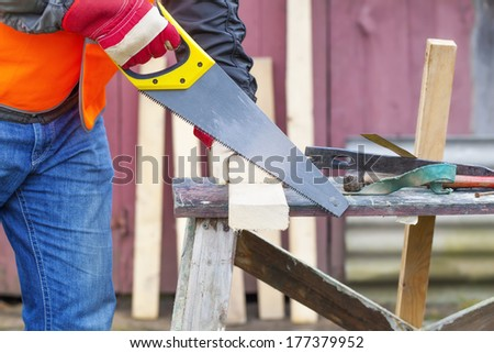 Carpenter sawing plank on to the work table - stock photo