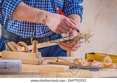 carpenter scetching wooden plank construction concept  - stock photo