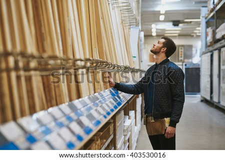 Carpenter selecting wood in a hardware store or warehouse standing looking at cut lengths on a rack, side view - stock photo