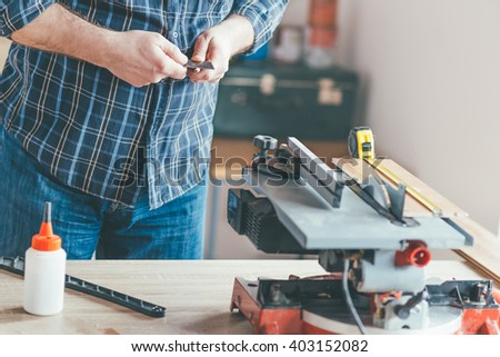 Carpenter sharp wooden pen in his workshop. Selective focus and small depth of filed.