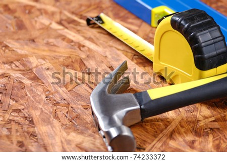 Carpenter tools over hardboard - stock photo