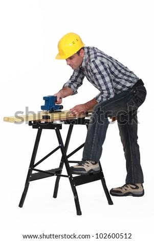 Carpenter using an electric sander - stock photo