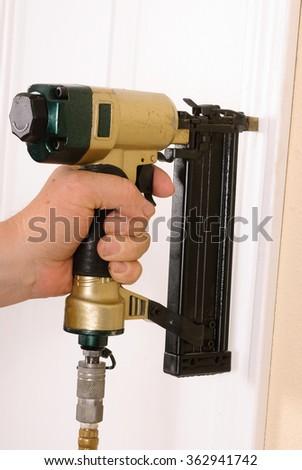 Carpenter using nail gun to complete door framing trim - stock photo