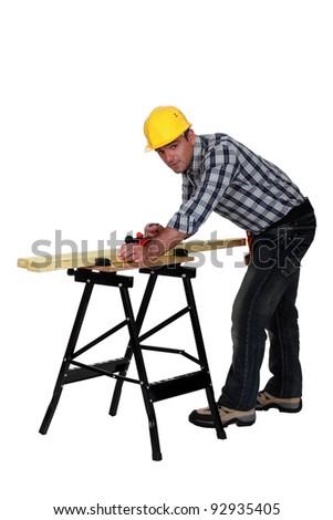 Carpenter using plane - stock photo