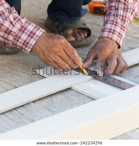 carpenter using ruler to draw a line marking on a wood board - stock photo