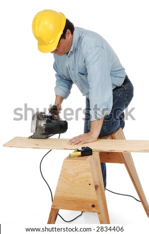 Carpenter wearing hard hat cutting a plank on a saw horse with a power saw. - stock photo
