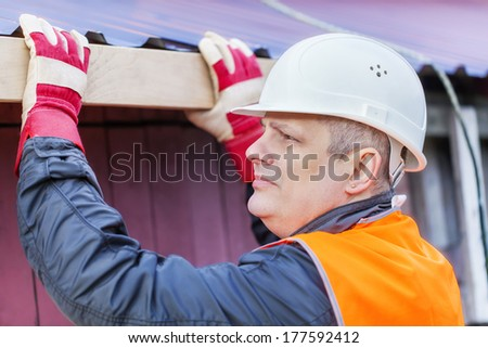 Carpenter with a wooden board near the roof - stock photo