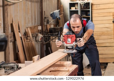 Carpenter with an electric router, horizontal shot