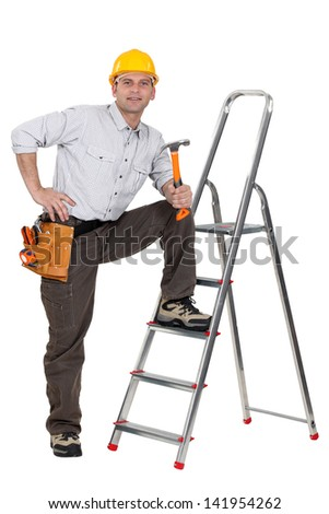 carpenter with leg resting on ladder holding hammer - stock photo