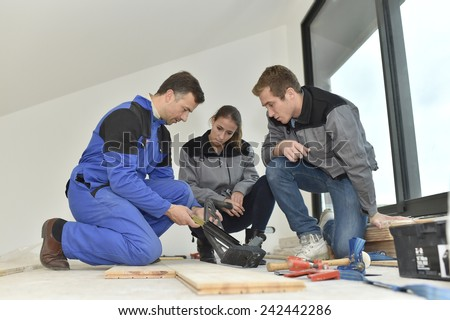 Carpenter with trainees installing wooden floor - stock photo