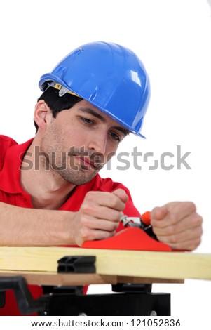 Carpenter with wood plane - stock photo