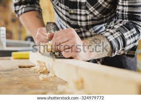 Carpenter work with plane on wood plank - stock photo