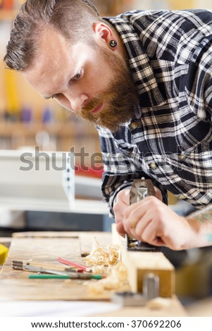 Carpenter work with planer on wood plank in workshop - stock photo