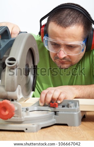 Carpenter worker cutting wood with electric saw - closeup