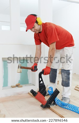 carpenter worker installing wood floor parquet board during flooring work with hammer - stock photo