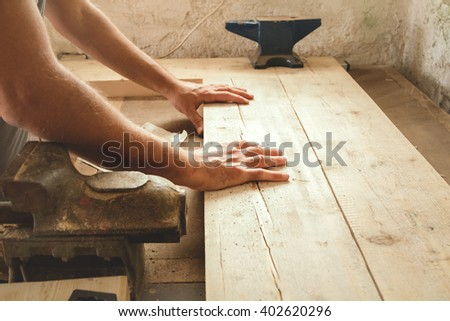 "Carpenter working hard in his small ""office"". - stock photo"