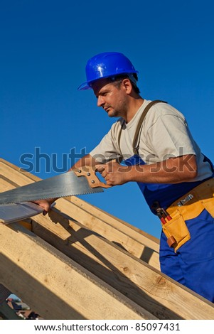 Carpenter working on the roof with a saw - stock photo