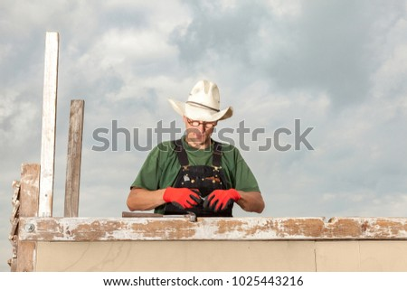carpenter working outside on a wooden construction for a summerhouse