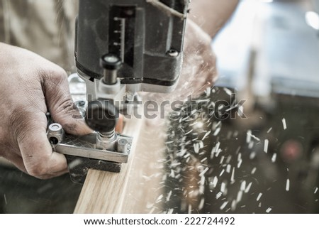 Carpenter working over door edge, creating hinges holes, blurred motion - stock photo