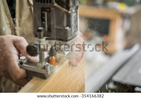 Carpenter working over door edge, creating hinges holes, blurred motion