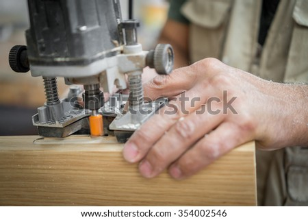 Carpenter working over door edge, making hinges holes, blurred motion - stock photo