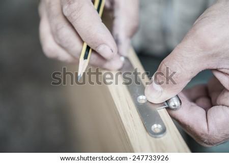 Carpenter working over door edge, shallow depth of field - stock photo