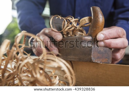 carpenter working with plane on wooden background - stock photo