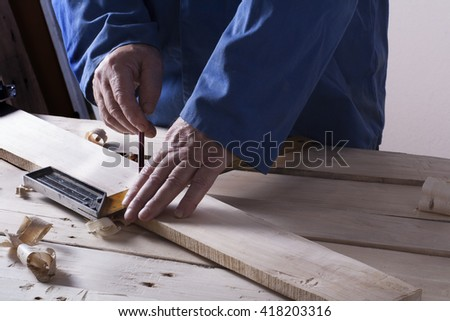 Carpenter working with plane on wooden background at Building Site. Joiner workplace. - stock photo