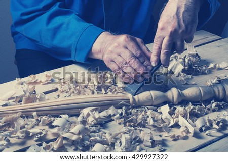 Carpenter working with plane on wooden background at Building Site. Joiner workplace - stock photo